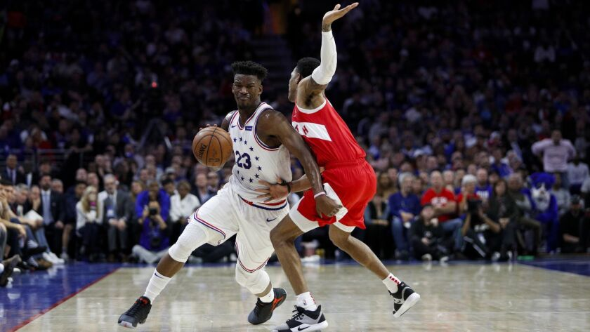 Philadelphia 76ers' Jimmy Butler, left, tries to get past Toronto Raptors' Patrick McCaw during the
