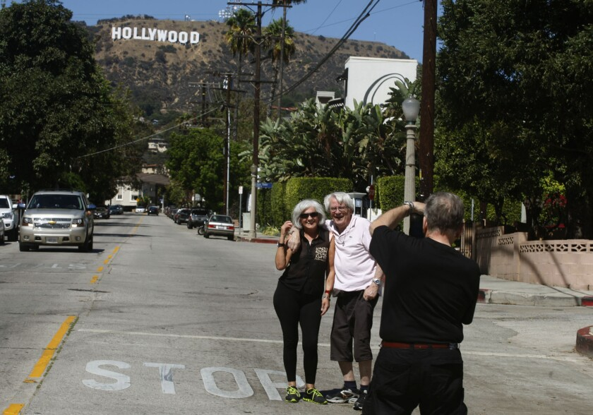Tourists pose beneath the Hollywood sign in the Beachwood Drive area, near the Hollywood Hills inter
