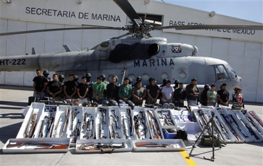 Members of the navy escort alleged members of the Golf drug cartel as they are presented to the press with seized weapons in Mexico City, Wednesday Sept. 29, 2010. The suspects were detained during the last 24 hours in different operations in the border cities of Matamoros and Reynosa, northern Mexico, navy officials said. (AP Photo/Claudio Cruz)