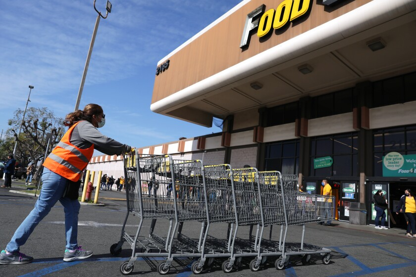 A grocery worker collects carts outside of the Food 4 Less on South Street in North Long Beach.