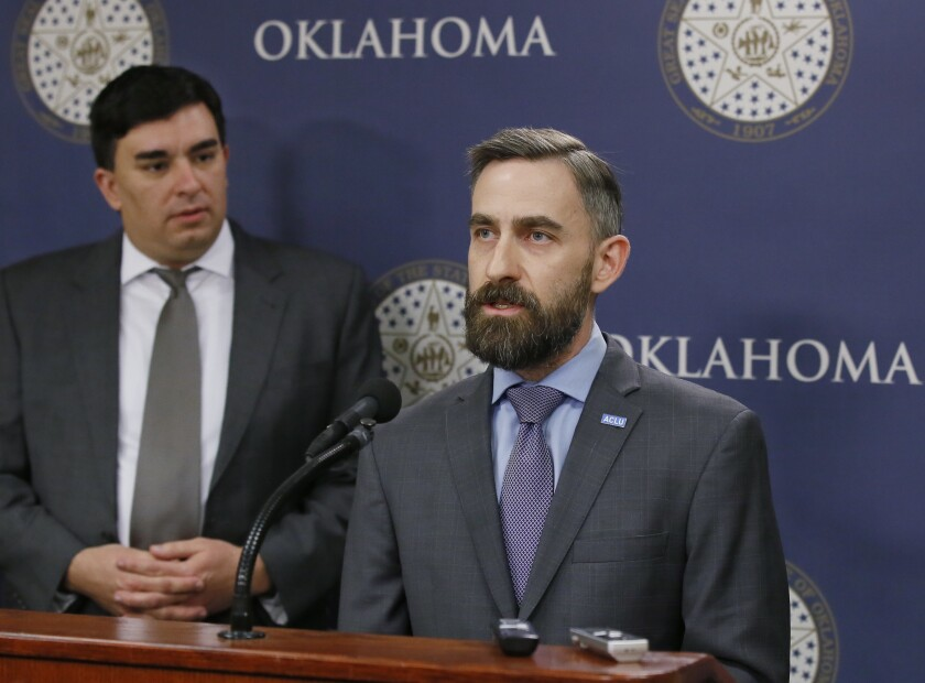 FILE - In this Feb. 7, 2017 file photo, Ryan Kiesel, right, Executive Director of the American Civil Liberties Union of Oklahoma, speaks during a news conference in Oklahoma City. At left is Brady Henderson, Legal Director. The American Civil Liberties Union of Oklahoma has filed a federal class-action lawsuit Tuesday, Dec. 10, 2019, against court officials in Canadian County, alleging their bail system unconstitutionally discriminates against poor and disabled people. (AP Photo/Sue Ogrocki, File)