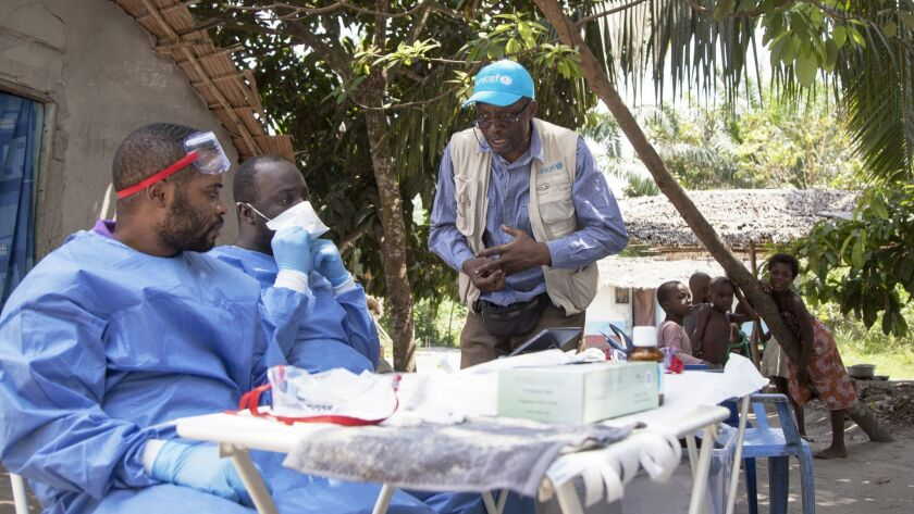 In this photo taken Friday, May 25, 2018, UNICEF staffer Jean Claude Nzengu, center, talks with memb