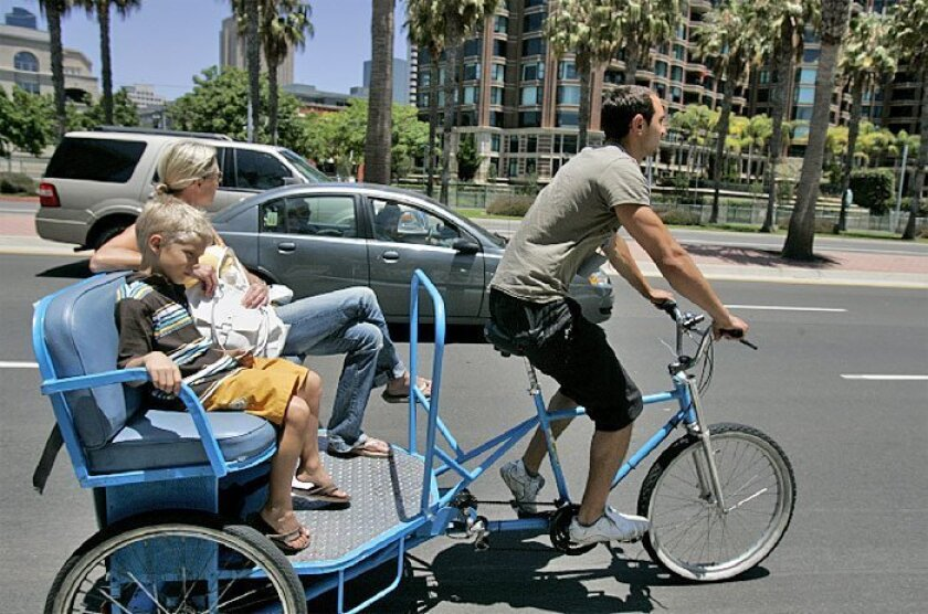 Amie Mitchell, of Huntington Beach, and her son, Johnny, 6, rode in a pedicab driven by Murat Gokkur on Harbor Drive. Proposed regulations would limit the roads that pedicabs could travel. (Laura Embry / Union-Tribune)