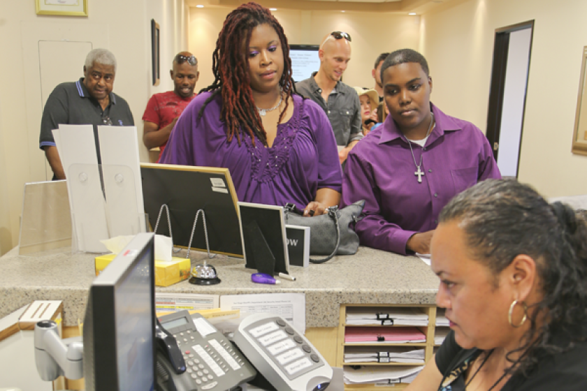 Rika Grier, left, and her partner Pastor Nicki Fairley, wait to obtain a license from the San Diego County marriage bureau. The San Diego County clerk is seeking to block the issuance of marriage licenses for same-sex couples.