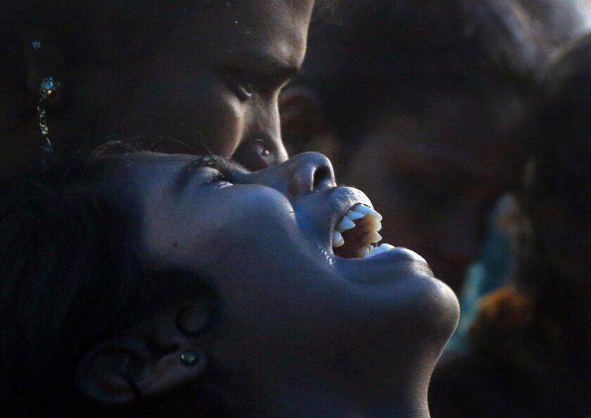 An Indian woman cries over the death of her family member who died after drinking tainted liquor at his funeral in Mumbai, India, Saturday, June 20, 2015. The death toll from drinking tainted liquor in a Mumbai slum climbed to more than 80 in the worst incident of its kind in more than a decade, po