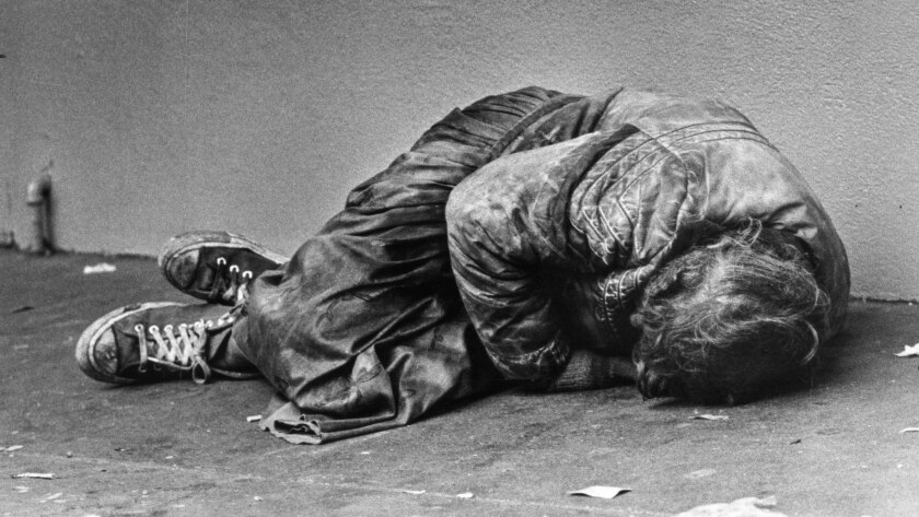 Nov. 21, 1985: A sleeping man pulls himself into fetal position for extra warmth before dawn on cold sidewalk on Hill Street in downtown Los Angeles.