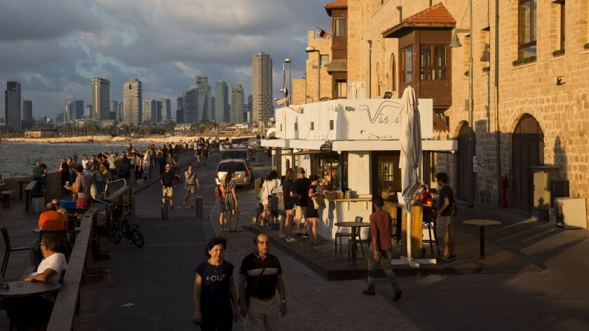 In this Saturday, July 28, 2018 photo, people enjoy the day on Jaffa's promenade overlooking Tel Avi