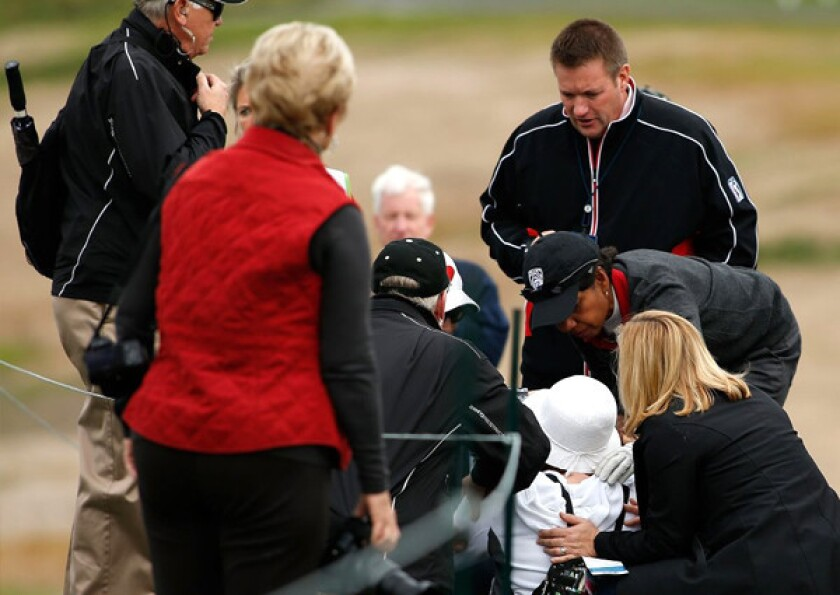Condoleezza Rice bends down to check on a woman (in white) who was hit by Rice's wayward shot.