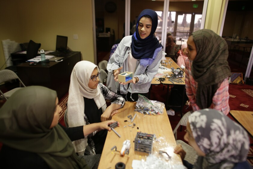 During a practice in September, coach Zaina Siyed explains what team members need to transport a shark toy with their Lego robot. All the team members wear hijabs inside the mosque where they practice.