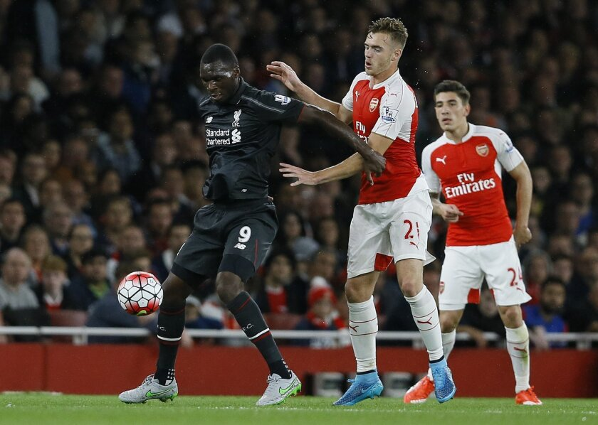 Arsenal's Calum Chambers, centre, vies for the ball with Liverpool's Christian Benteke during the English Premier League soccer match between Arsenal and Liverpool at Emirates stadium in London, Monday, Aug. 24, 2015. (AP Photo/Kirsty Wigglesworth)