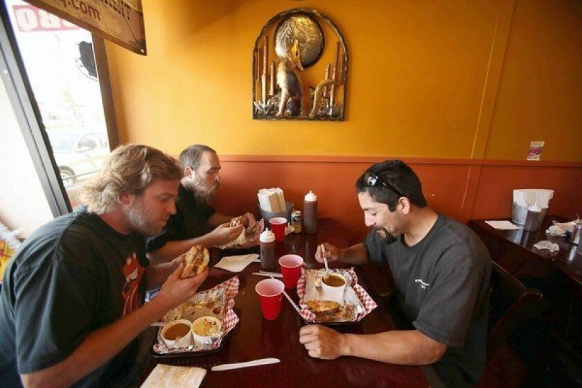 Dan Horton, left, Anthony White and Richard Navarro have lunch in August at Smokin' Jonny's BBQ in Gardena. Owner Jon Sekiguchi says he's selling beef ribs only on the weekends, when customers are more willing to splurge. He also says he's struggling to find affordable beef sausage for his $6.95 smoked sausage sandwich.