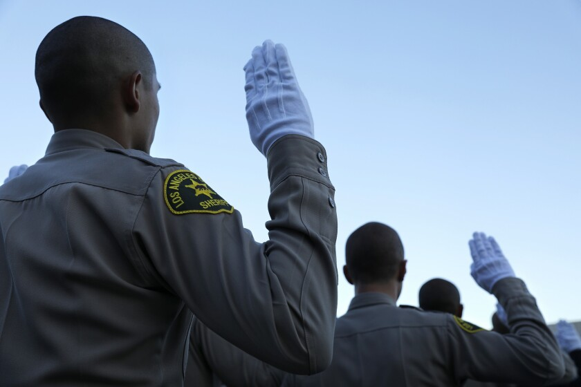 Los Angeles County sheriff's deputies raise their right hands during their graduation ceremony in 2017.
