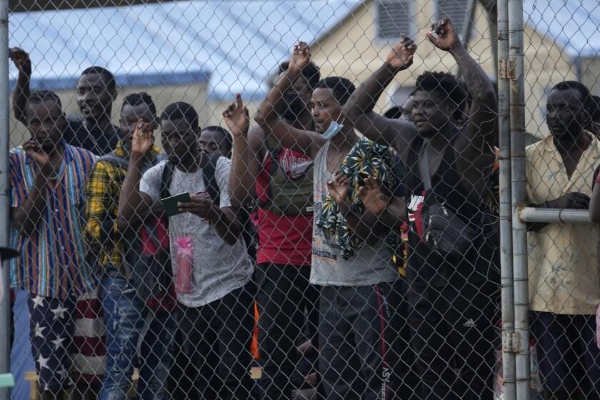 En esta fotografía del 5 de agosto de 2021, los migrantes --mayormente haitianos-- se paran detrás de una cerca de alambre en un campamento mientras ven a otros migrantes subir a un autobús que los llevará a otro lado del país, cerca de la frontera con Costa Rica, en San Vicente, provincia de Darién, Panamá, cerca de la frontera con Colombia. La canciller panameña Erika Mouynes dijo el lunes 20 de septiembre a la AP que Panamá solicitará ayuda internacional durante la Asamblea General de las Naciones Unidas para atender ese masivo flujo irregular. (Foto AP/Arnulfo Franco, Archivo)