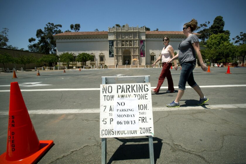 "Naomi Labbe and Rachel Lang (right) walk through the Balboa Park's Plaza de Panama where ""No Parking"" signs have been posted effective from the 10th up to the 21st of June."
