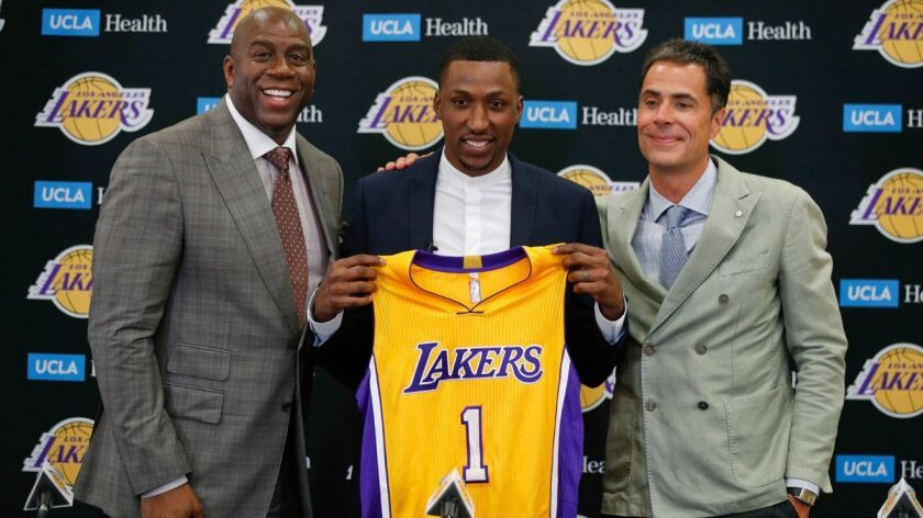 Lakers' Kentavious Caldwell-Pope, center, poses for photos with Magic Johnson, left, and general man