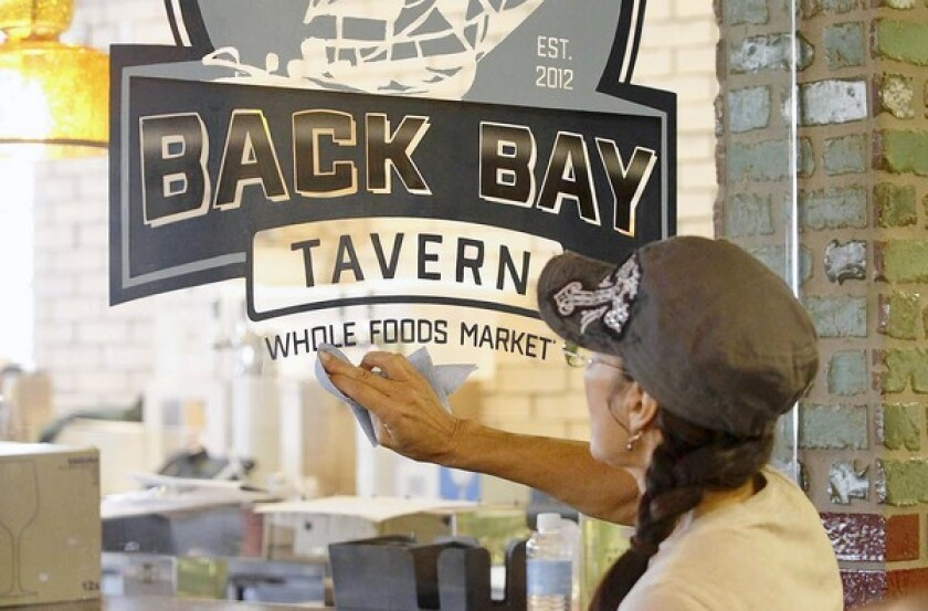 Darcie Copeland shines the hand-cut vinyl letters to the new Back Bay Tavern window Thursday as she readies the Whole Foods Market for its grand opening at Newport Beach's Fashion Island on Sept. 19.