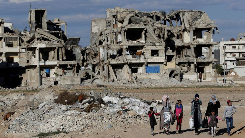 In this March 31, 2018 photo, Syrian citizens walk in front of buildings that were destroyed during