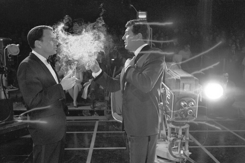 """Frank Sinatra, left, and Dean Martin on an NBC set in the photo '1962 — Smokin'. Frank and Dean"""" from the book """"The Rat Pack."""""""