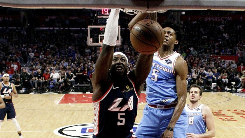 Clippers center Montrezl Harrell dunks against the Kings during the second half Sunday.