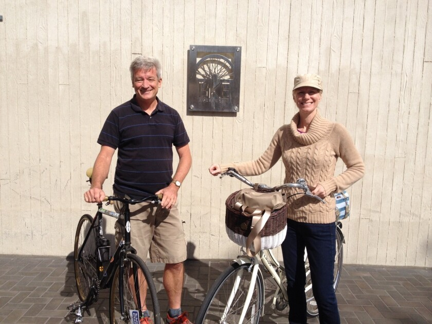 Cycling advocates Charlie Gandy and Melissa Balmer show off a plaque designating Long Beach as the most bicycle-friendly city in America.