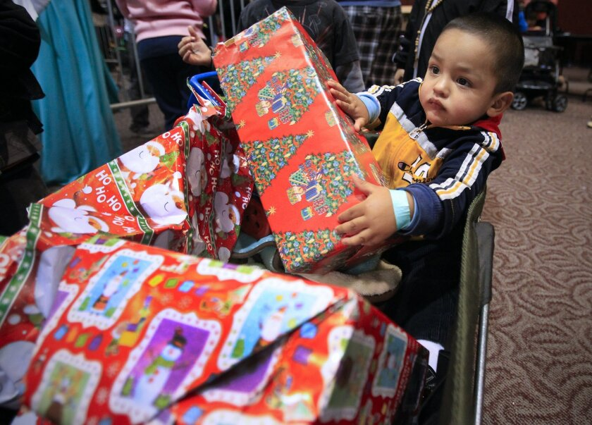 "Derek Diaz, 2,  is surrounded by the gifts he and his brothers received during the annual ""Holiday Magic for Kids"" Christmas party sponsored by the San Diego Coalition for the Homeless and held at Golden Hall."