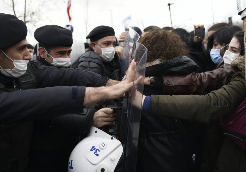 Turkish police officers clash with students of the Bogazici University protesting the appointment of a government loyalist to head their university, in Istanbul, Tuesday, Feb. 2, 2021. For weeks, students and faculty at Istanbul's prestigious Bogazici University have been protesting President Recep Tayyip Erdogan's appointment of Melih Bulu, a figure who has links to his ruling party, as the university's rector. They have been calling for Bulu's resignation and for the university to be allowed to elect its own president. (AP Photo/Omer Kuscu)