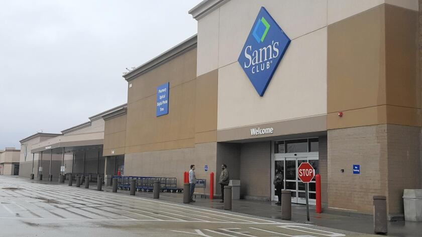 Security guards outside the Sam's Club on Route 59 in Naperville speak to a customer about the store being closed Thursday and closing for good on Jan. 26.