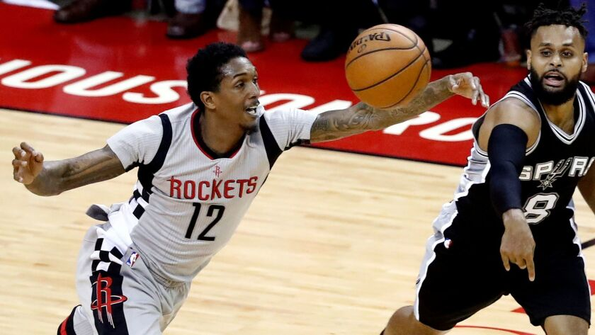 Guard Lou Williams (12) goes for a loose ball in a Houston Rockets game against San Antonio's Patty