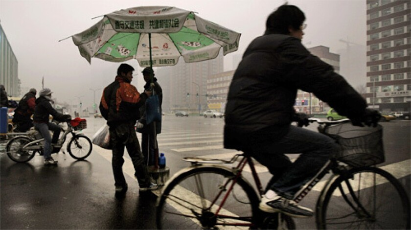 """GLOOMY: People ride bikes on a damp day in Beijing last month. The real rainy season comes in summer, and Chinese meteorologists have trained for the Summer Olympics by practicing their """"rain mitigation"""" techniques at recent special events. They've had several successes."""