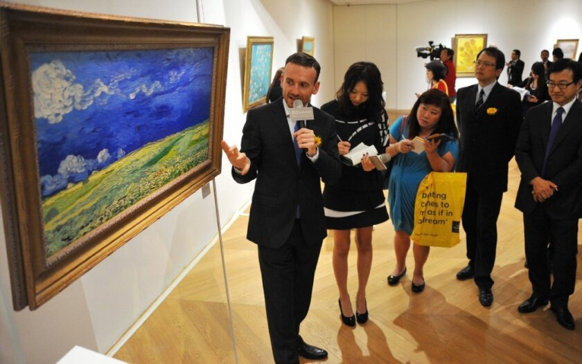 """Van Gogh Museum director Axel Ruger, left, shows a copy of """"Wheatfield under Thunderclouds"""" to reporters in Taipei, Taiwan."""