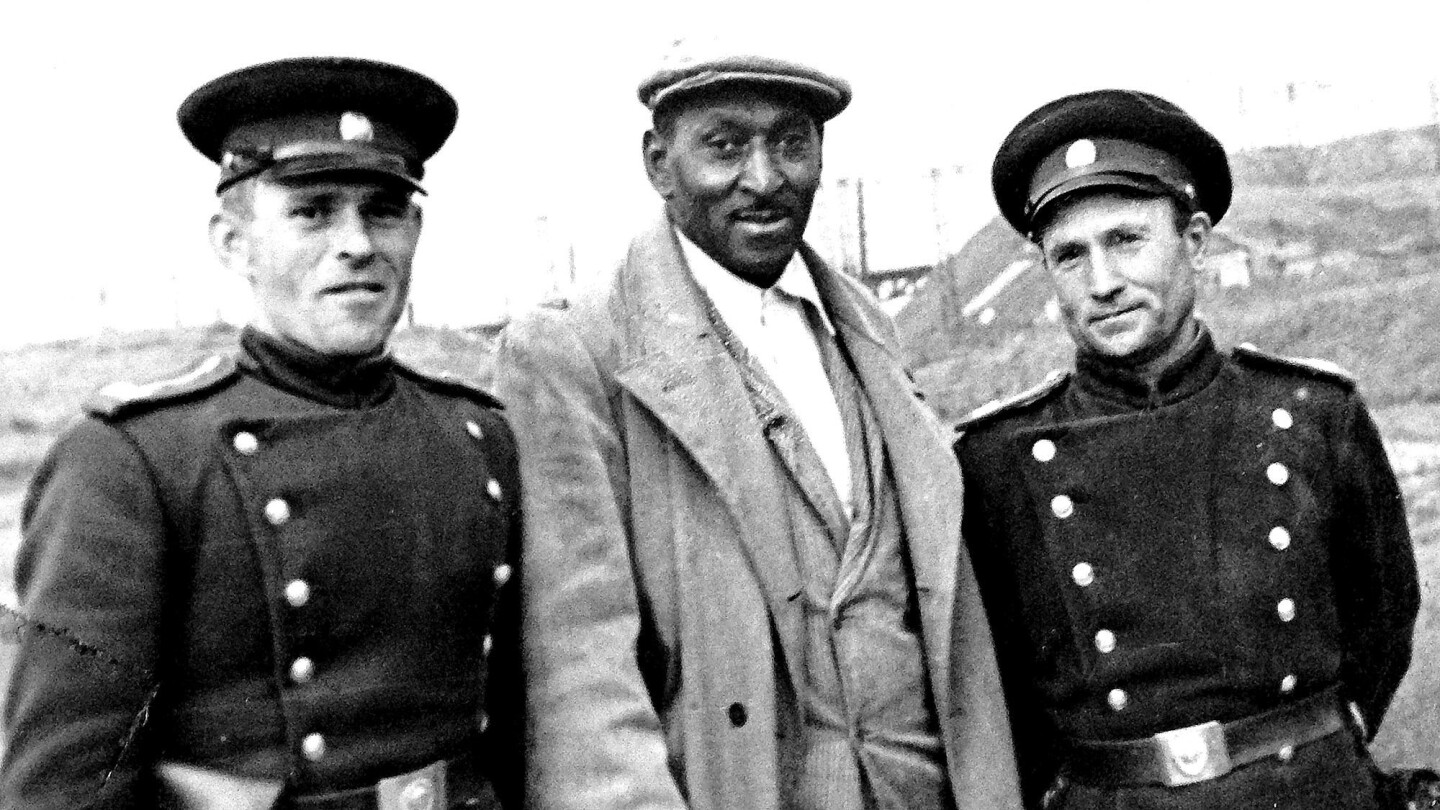 Agronomist George Tynes, flanked by Soviet army cadets, was among several hundred African Americans who traveled to the Soviet Union to work in the 1930s. Some settled there and became citizens.
