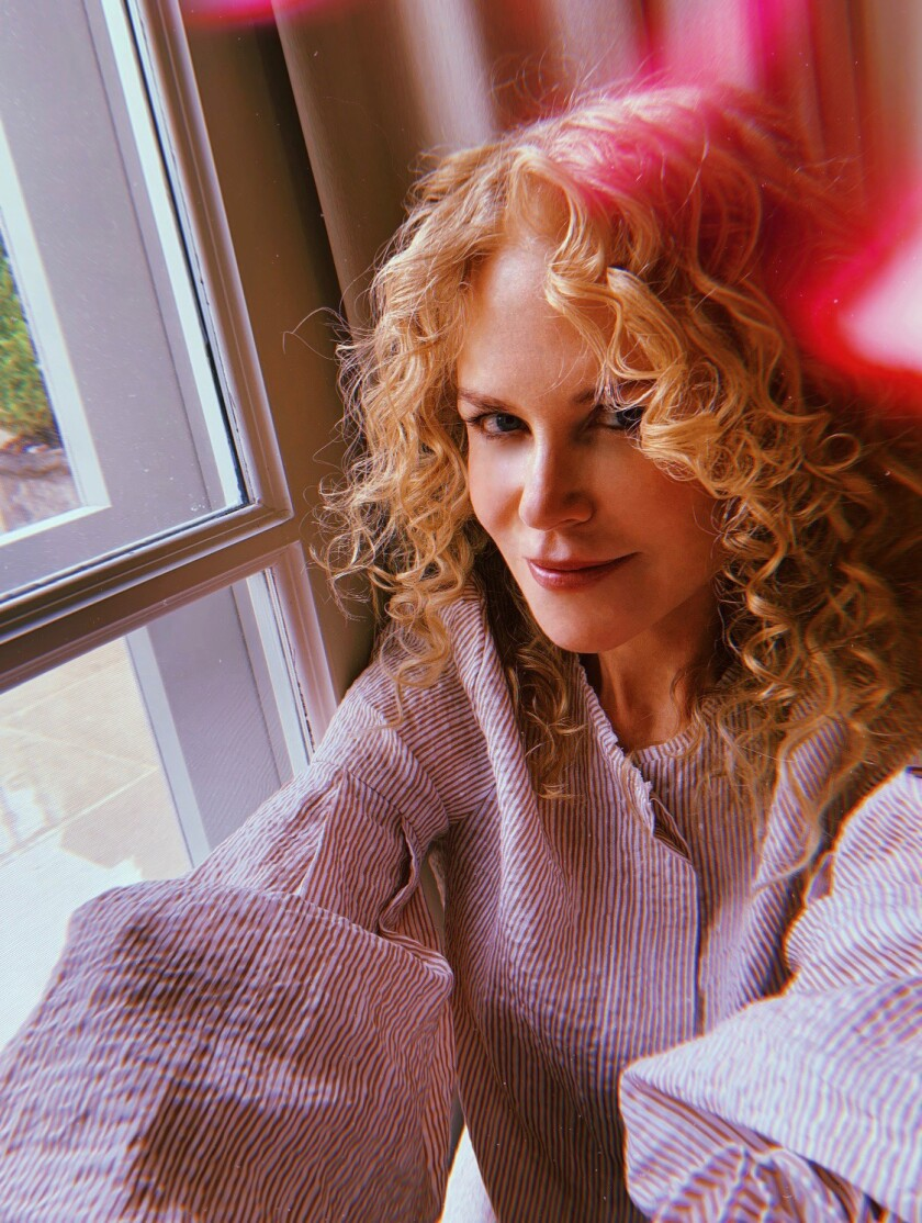 A woman with curly hair sits at a window