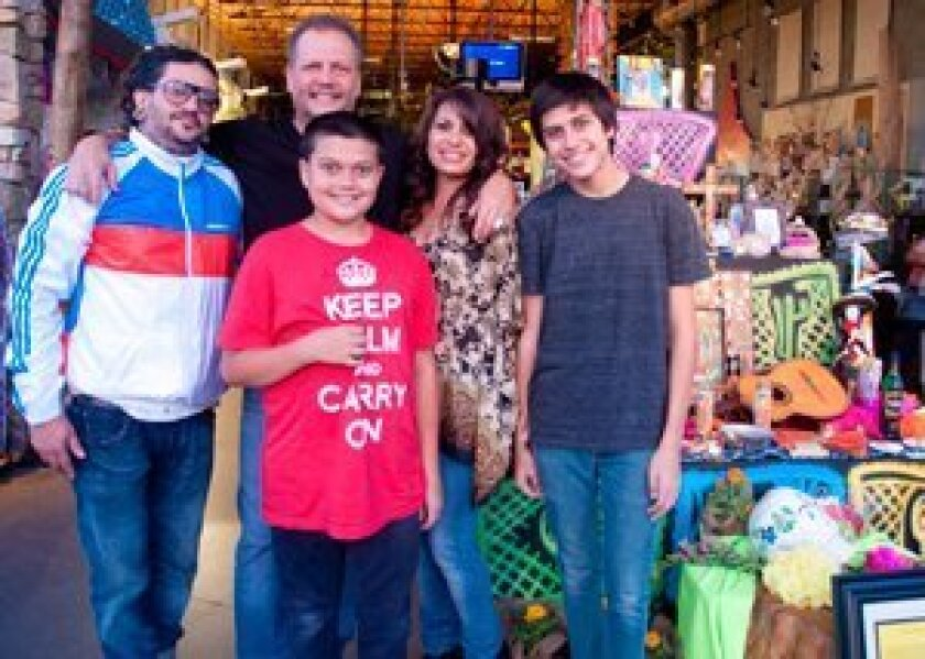 Artist Todd Swenke (right) stands by his altar with his family, Carla, Quentin and Todd Jr. and musician Karlos Paez