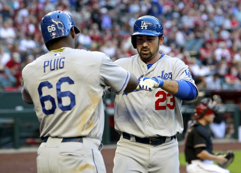 Dodgers first baseman Adrian Gonzalez is congratuled by right fielder Yasiel Puig after hitting a two-run home run against the Diamondbacks in the third inning Saturday night in Phoenix.