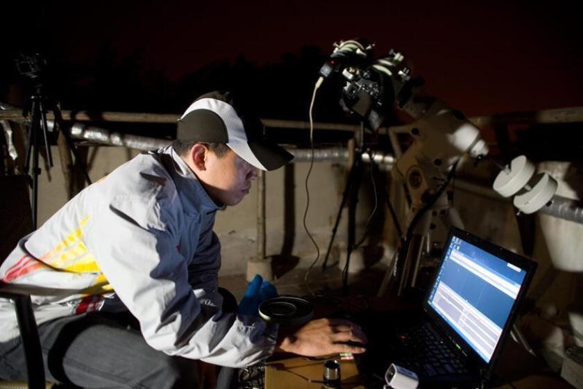Un empleado del observatorio de Qingdao (China) observa el eclipse total de Luna. EFE/Archivo