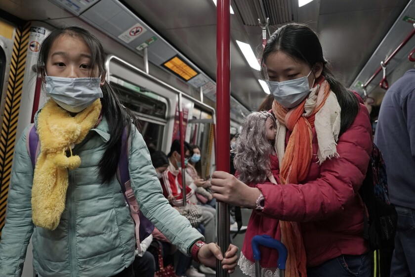 Two girls with face masks ride the subway in Hong Kong