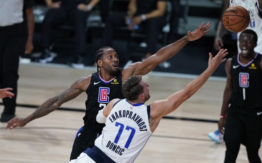 Clippers forward Kawhi Leonard, top, fouls Dallas Mavericks guard Luka Doncic.