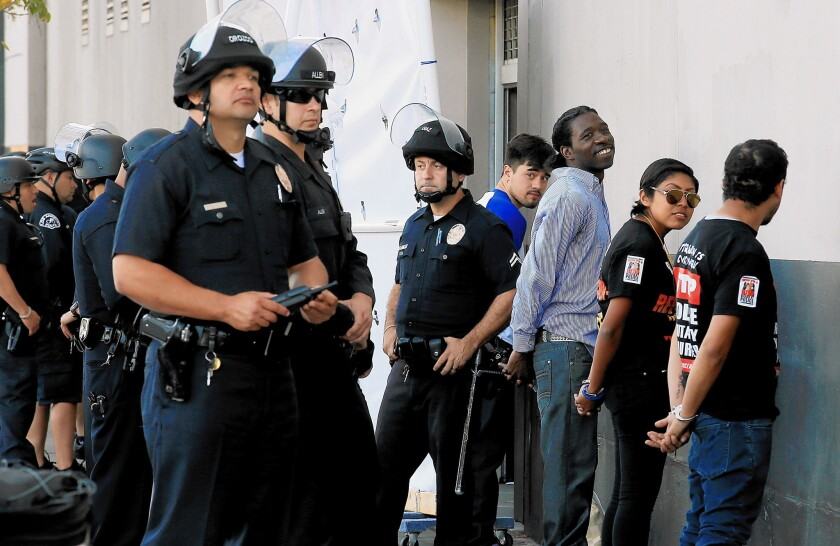 LAPD officers detain about a dozen anti-police brutality protestors in downtown Los Angeles