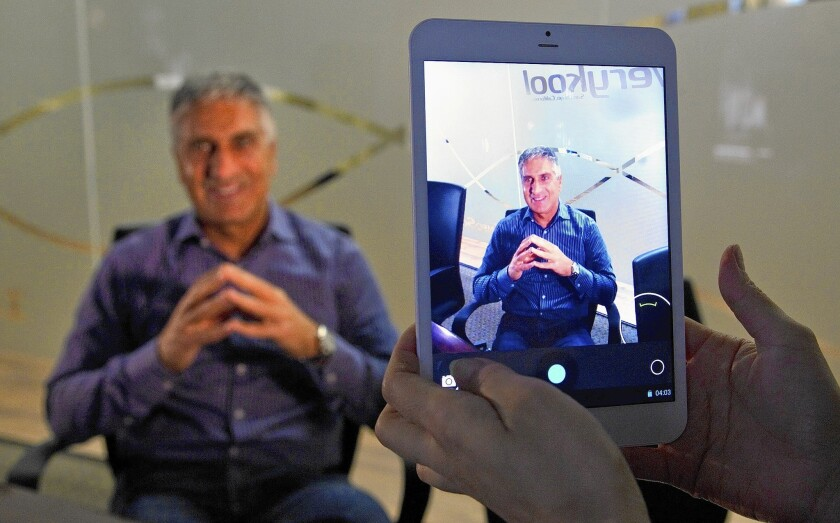 Joseph Ram, president and CEO of InfoSonics seen through the company's new HD 8-inch tablet.