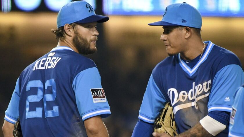 Los Angeles Dodgers' pitcher Clayton Kershaw, left, and shortstop Manny Machado talk on the mound during a baseball game against the San Diego Padres, Saturday, Aug. 25, 2018, in Los Angeles.