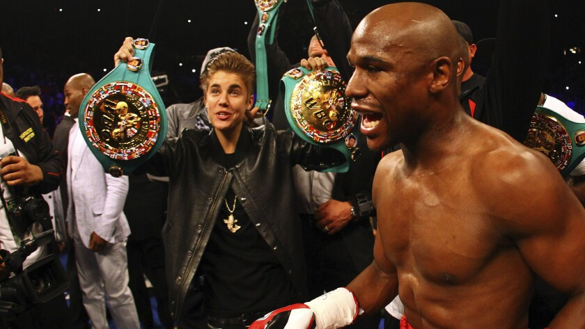 Recording artist Justin Bieber, left, holds up a pair of championship belts before Floyd Mayweather Jr.'s fight against Miguel Cotto at the MGM Grand in Las Vegas on May 5, 2012.