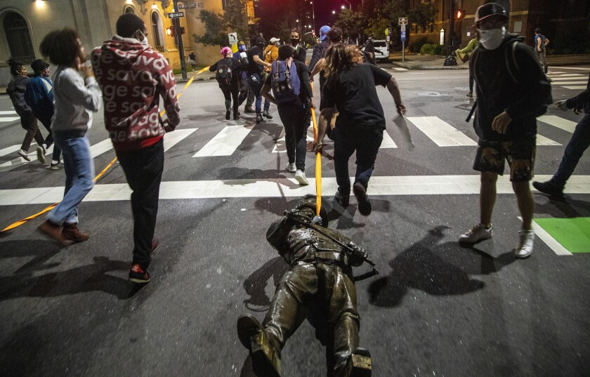 Protesters drag a figure pulled from the Confederate monument at the State Capitol down Salisbury Street in Raleigh, N.C., on Juneteenth, Friday, June 19, 2020. (Travis Long/The News & Observer via AP)