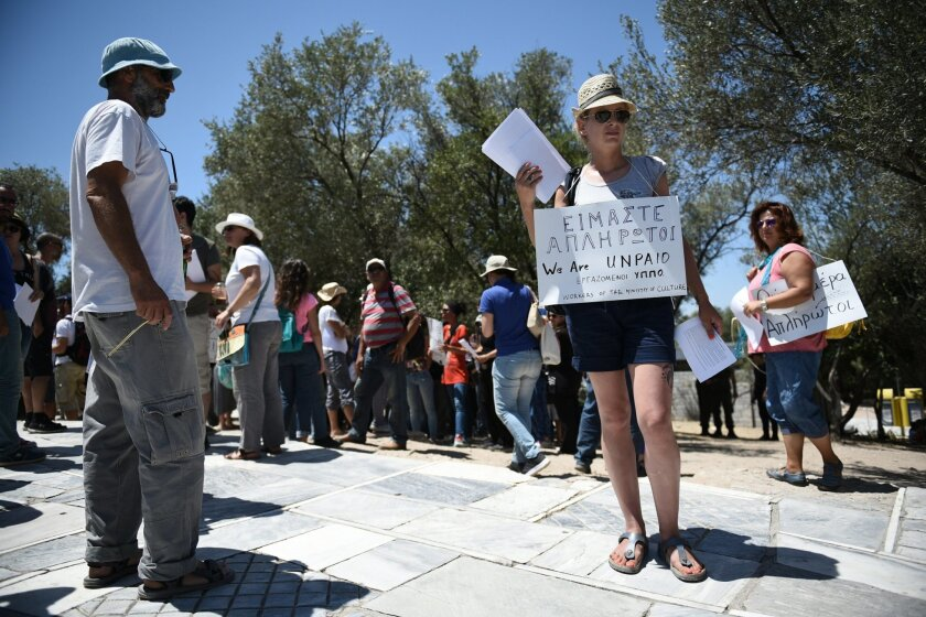 "Short-term contract employees of the Culture Ministry, unpaid for over six months, inform tourists about their protest outside the entrance of the ancient Acropolis hill in Athens, Thursday, July 23, 2015. Greece's radical left-led government survived another revolt by rebels in the early hours of Thursday, passing reforms that should pave the way for the imminent start of bailout discussions with European creditors. Sign reads in Greek and English ""We are unpaid"". (AP Photo/Giannis Papanikos)"
