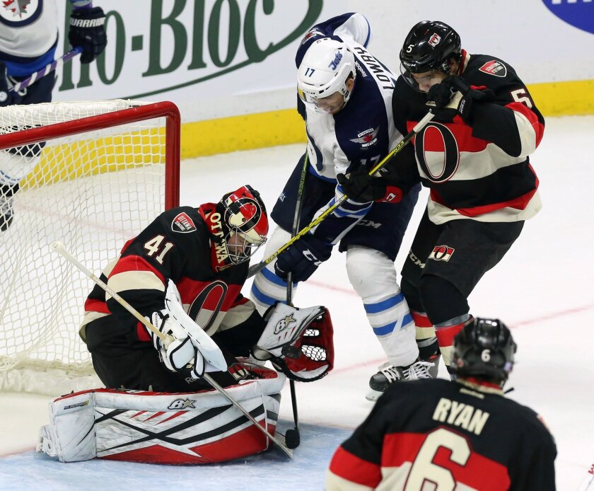 Ottawa Senators goaltender Craig Anderson (41) attempts to shield the puck in front of teammate Cody Ceci (5) and Winnipeg Jets' Adam Lowry (17) during the second period of an NHL hockey game Thursday, Nov. 5, 2015, in Ottawa, Ontario. (Fred Chartrand/The Canadian Press via AP)