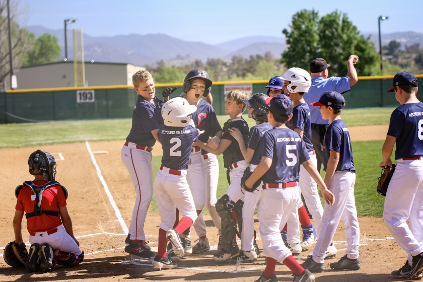Tallon Ogilvie, a player in the Broncos division, celebrates with teammates after hitting a home run opening day April 10.