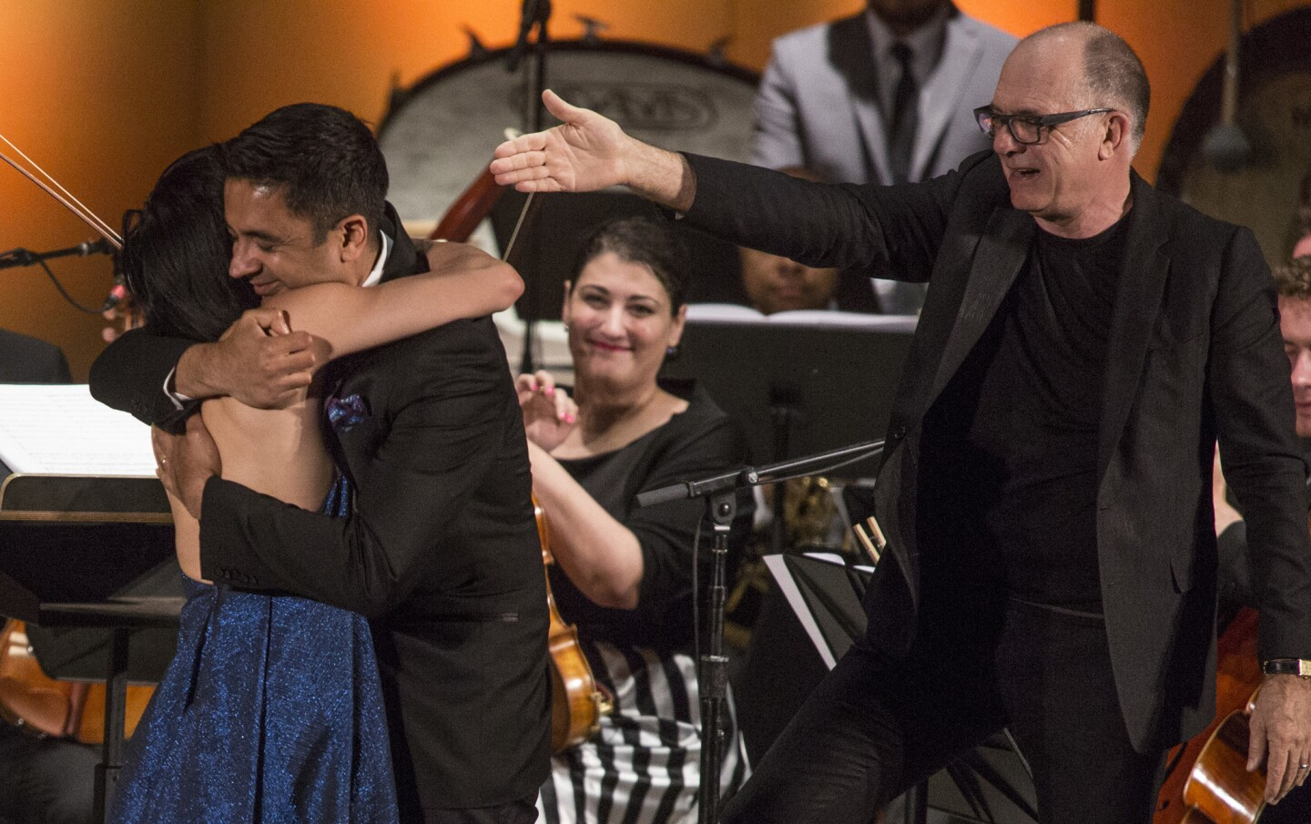 """Conductor Steven Schick acknowledges Vijay Iyer as he hugs violinist Jennifer Koh after performance of Iyer's """"Trouble"""" at the Ojai Music Festival's opening night June 8, 2017."""