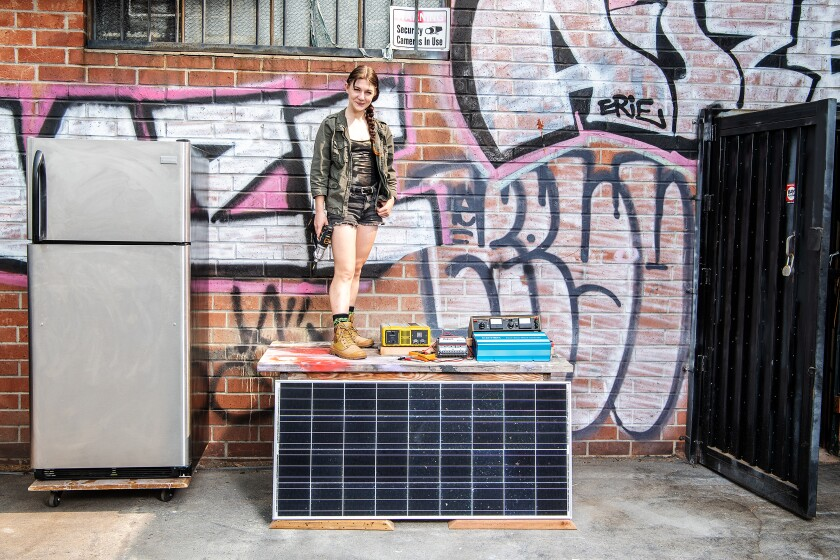 Bee Burlingame poses outside her workspace with the materials she will use to create L.A.'s first solar community fridge.