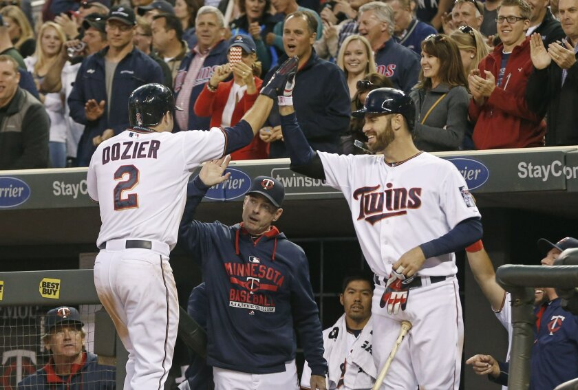 Minnesota Twins' Joe Mauer, right, congratulates Brian Dozier, left, after his three-run home run off Chicago White Sox starting pitcher Chris Sale in the third inning of a baseball game, Thursday, April 30, 2015, in Minneapolis. (AP Photo/Jim Mone)