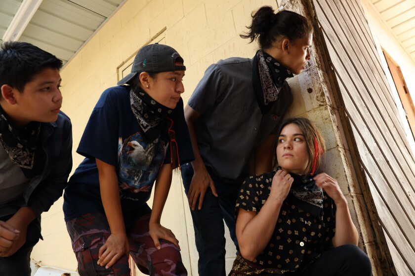 A group of teens crouch at the corner of a building