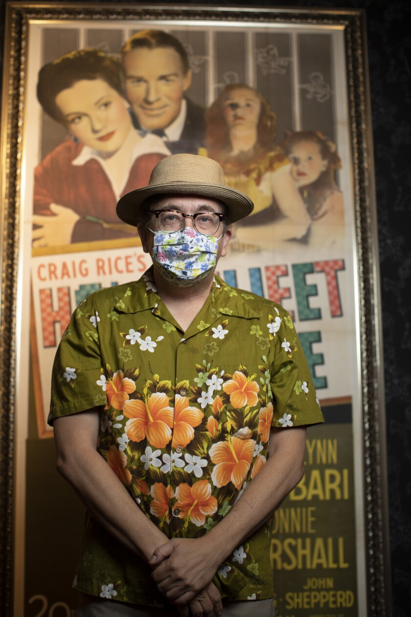 A man in a mask, hat and floral print short-sleeved shirt stands in front of a movie poster.